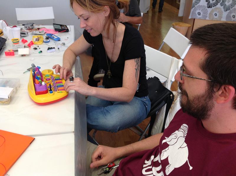 Eugenio e Sara alle prese col giocattolo sonoro del loro bambino. Alla fine della giornata suonerà qualcosa di molto diverso